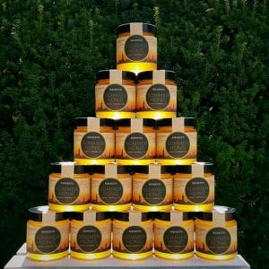 Goldgelb leuchtende Honiggläser bilden eine Honigpyramide