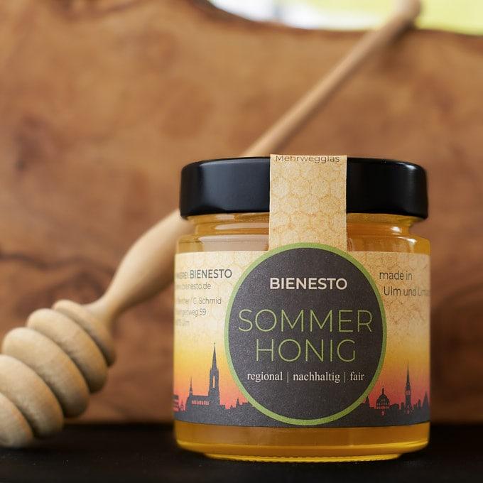 Foto des flüssigen Sommerhonigs mit Honiglöffel