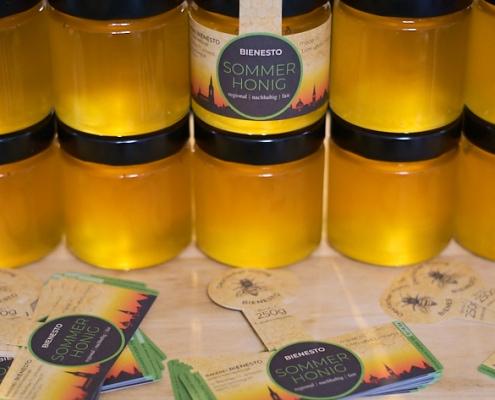 Foto von Honiggläsern und Etiketten als Beispiel für Firmenhonig mit eigenem Etikett