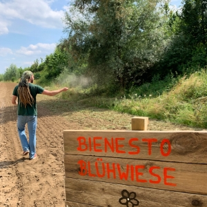 Foto einer Bienesto-Blühwiese mit Schild und im Hintergrund ein Acker mit Chris der gerade eine Blühfläche aussäät.