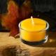 Teelicht aus Bienenwachs im Glas ohne Alu mit Ahornblatt im Hintergrund für eine gemütliche Atmosphäre.
